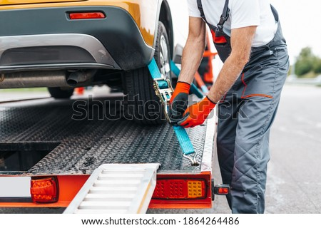 Handsome senior man working in towing service on the road. Roadside assistance concept. Royalty-Free Stock Photo #1864264486