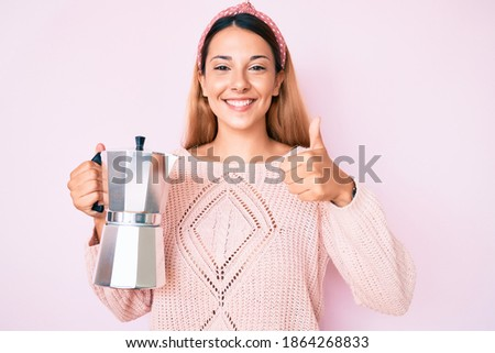 Young brunette woman holding italian coffee maker smiling happy and positive, thumb up doing excellent and approval sign