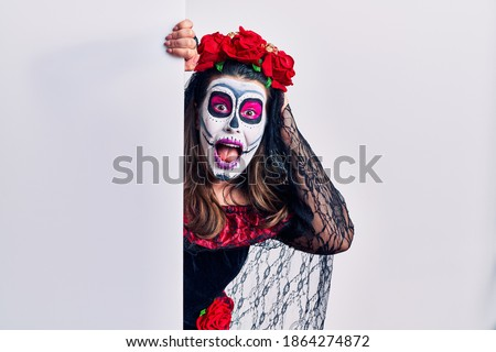 Young woman wearing day of the dead custome holding blank empty banner crazy and scared with hands on head, afraid and surprised of shock with open mouth