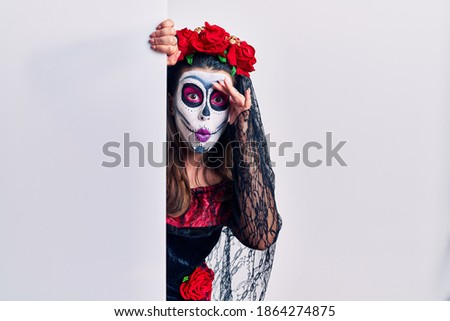 Young woman wearing day of the dead custome holding blank empty banner worried and stressed about a problem with hand on forehead, nervous and anxious for crisis