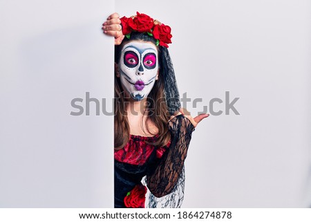 Young woman wearing day of the dead custome holding blank empty banner surprised pointing with hand finger to the side, open mouth amazed expression.