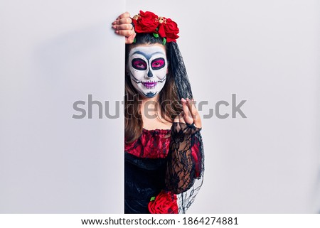Young woman wearing day of the dead custome holding blank empty banner doing money gesture with hands, asking for salary payment, millionaire business