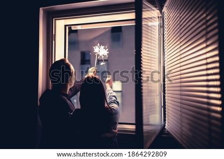 Couple holding sparklers out of the window at night. New year's eve celebration, anniversary, party or date at home. Spontaneous candid fun with light firework stick. Happy and playful romantic moment Royalty-Free Stock Photo #1864292809
