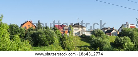 A lawn with green grass all the way to the horizon. Horizontal landscape of a flat field with fresh spring grass. Village, country houses, SNT, on the background of fields and trees. Royalty-Free Stock Photo #1864312774