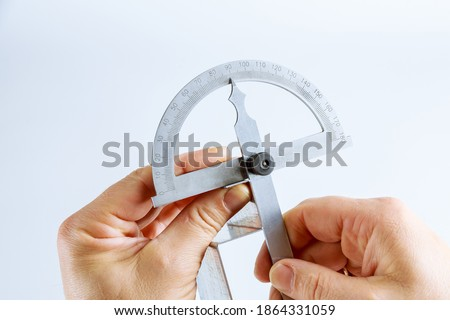 The worker measures the angle on the metal product with a digital protractor.
