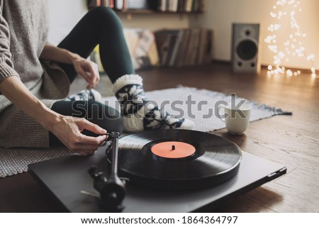Woman listening music, relaxing, enjoying life at home. Girl wearing warm winter clothes having fun. Turntable playing vinyl LP record. Leisure, Christmas time, lockdown, retro revival, lifestyle