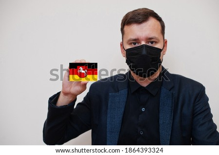 German man wear black formal and protect face mask, hold Lower Saxony flag card isolated on white background. Germany states coronavirus Covid concept. Royalty-Free Stock Photo #1864393324