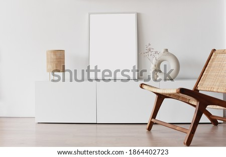 Blank picture frame mockup on white wall. Living room design. Empty white copy space for artwork. View of modern scandinavian style interior with chair. Home staging and minimalism concept Royalty-Free Stock Photo #1864402723