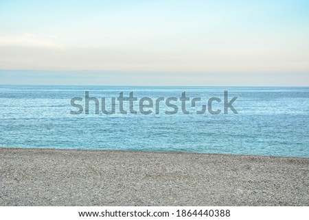 Beautiful Calm turquoise sea beach with soft orange evening sky background. Relaxation and leisure nature background