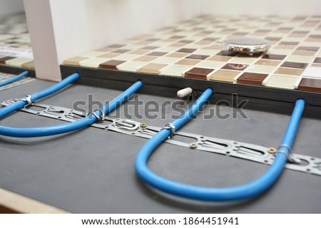 Installing a radiant floor heating system with a close up of heating cables fastened to the floor underlayment under ceramic mosaic bathroom floor while house renovation.   Royalty-Free Stock Photo #1864451941
