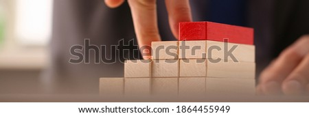 Focused photo on male person that playing with wooden blocks, making prototype of career enhancement