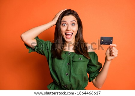 Photo of impressed funny lady wear green off-shoulders blouse arm head holding bank card isolated orange color background
