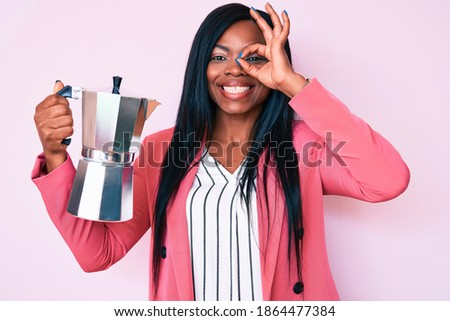 Young african american woman holding italian coffee maker smiling happy doing ok sign with hand on eye looking through fingers