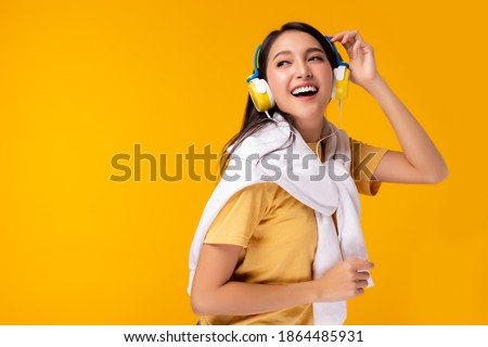 Gorgeous asian woman hanging sweater on shoulder and listening music in headphones and singing on yellow background. Charming girl dancing. Attractive lady enjoying favorite song. copy space Royalty-Free Stock Photo #1864485931
