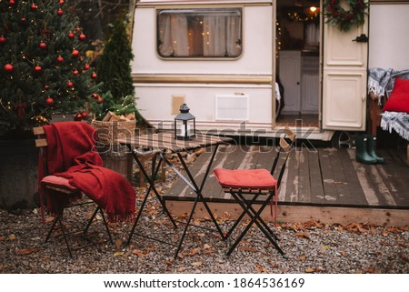 Caravan mobile home with terrace, Mobile home decorated with Christmas decor. Festive atmosphere - lights, red blankets, Christmas trees. Waiting for the snow. Caravan camping. mobile home trailer. Royalty-Free Stock Photo #1864536169
