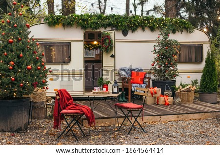 Caravan mobile home with terrace, Mobile home decorated with Christmas decor. Festive atmosphere - lights, red blankets, Christmas trees. Caravan camping. mobile home trailer. Selective focus #1864564414