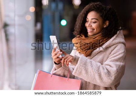 Online Shopping. Smiling black woman using her mobile phone, holding shopper bags, standing outdoors in the evening near mall, choosing clothes and presents, taking photo. Retail And Purchase