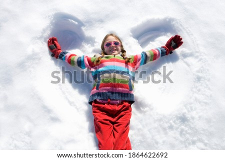 Little girl lying on snow and making a snow angel while looking up and smiling at the camera
