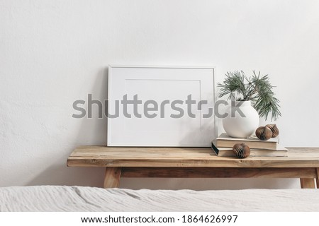 Winter still life. Horizontal white frame mockup on vintage wooden bench, table. Modern white ceramic vase with pine tree branches, Christmas paper ornaments and books. White wall background. Royalty-Free Stock Photo #1864626997