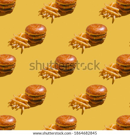 burger with fries on yellow background