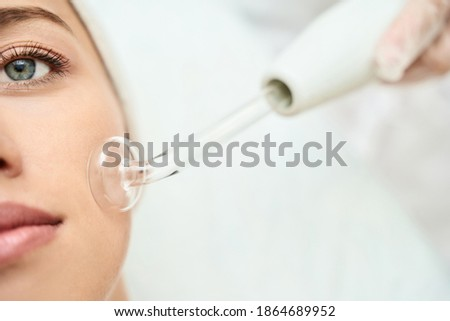 Darsonval cosmetology apparatus. Face cleaning procedure. Salon skincare treatment. Professional dermatology hardware. Electric spa equipment. Medicine patient device. Removal acne Royalty-Free Stock Photo #1864689952
