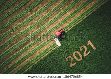 2021 Happy Ney Wear concept and red tractor mowing green field. Royalty-Free Stock Photo #1864706854