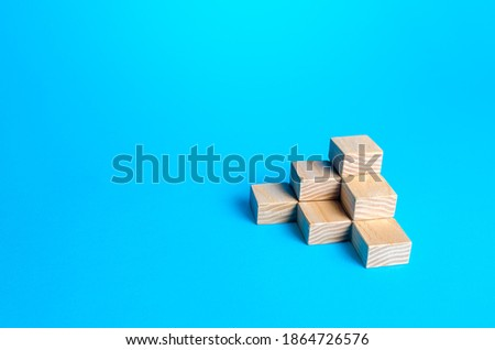Wooden blocks pyramid on a blue background. Minimalism. Simple shapes geometry. Slide for presentation. Copy space, place for text. Steps.