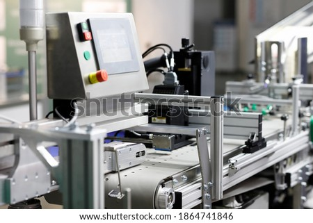 Automatic packaging belted conveyor system in a pharmaceutical plant. Selective focus. Royalty-Free Stock Photo #1864741846