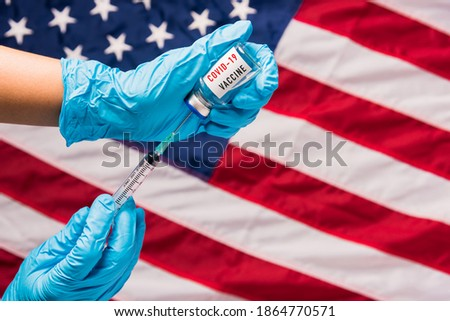Hands of doctor wear gloves holding coronavirus (COVID-19) vial vaccine and syringe on flag United States of America background, USA Vaccination Royalty-Free Stock Photo #1864770571