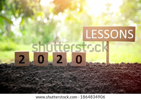 Life lessons and learnings from the year 2020 concept. A tree branch with a single remaining last leaf hanging beside a 2020 learning in wooden blocks at sunset.  Royalty-Free Stock Photo #1864834906