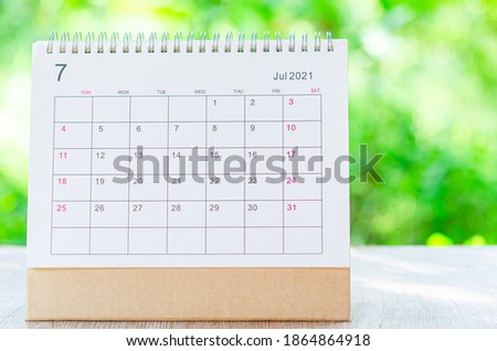 Calendar desk 2021 July month for organizer to plan and reminder on wooden table on nature background. Royalty-Free Stock Photo #1864864918