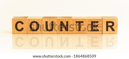 Wooden Blocks with the text: counter. The text is written in black letters and is reflected in the mirror surface of the table. New business relaunch startup concept.