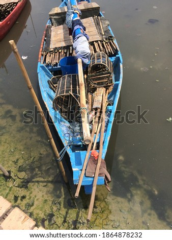 a traditional fishing boat that runs aground awaits the tide #1864878232