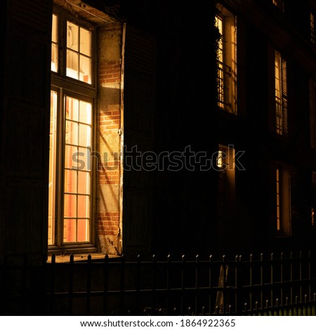 French house lit from inside. Dark facade at night and brightly lit windows. Small wooden gate in front of the house. Stones and exposed bricks. An autumn night in France. Square format Royalty-Free Stock Photo #1864922365