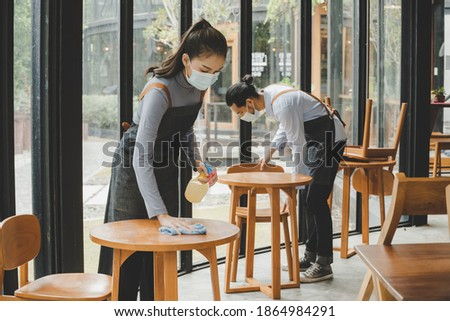 asian waitress staff wearing protection face mask in apron cleaning table with disinfectant spray for protect infection coronavirus (covid-19) in cafe coffee shop restaurant, hotel. new normal concept Royalty-Free Stock Photo #1864984291