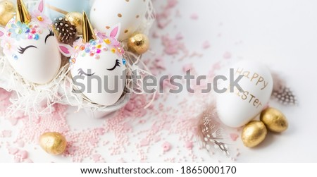 Banner. Easter eggs in the form of a unicorn, and with a gold pattern on a white background. Flat lay. Copy space for text.  Royalty-Free Stock Photo #1865000170
