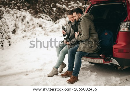 Beautiful young European couple in a sweater and jacket sitting on the trunk of a car and drinking tea with a thermos in the winter in the forest. Metal cup, rest, car trip, snow, bags, smartphone Royalty-Free Stock Photo #1865002456