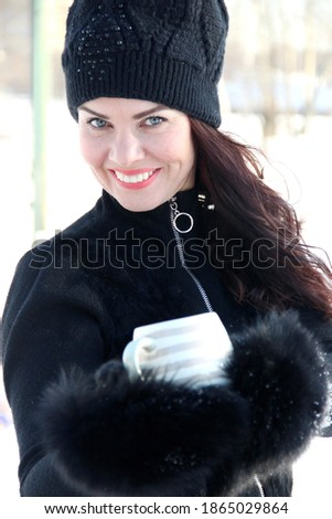 winter portrait of a beautiful blue-eyed brunette. an attractive woman in a black knitted hat with a pompom holds a beige striped Cup in black fur mittens, close-up. smile for a million Royalty-Free Stock Photo #1865029864