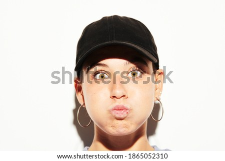 Stock photo of girl with hoop earrings wearing black cap making funny face and puffing out cheeks, white wall on background. Closeup young female fooling around