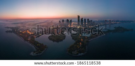 Aerial panoramic view of city waterfront highrise condo and business office buildings, constructions, marina, highways and roads by the lake halfway covered with fog at dusk. Royalty-Free Stock Photo #1865118538