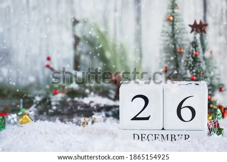 Kwanzaa. White wood calendar blocks with the date December 26th and Christmas decorations with snow. Selective focus with blurred background.