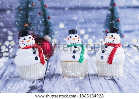 Three happy iced Christmas Snowman cupcakes with carrot nose, santa hat, and scarf. Selective focus with blurred foreground and background.