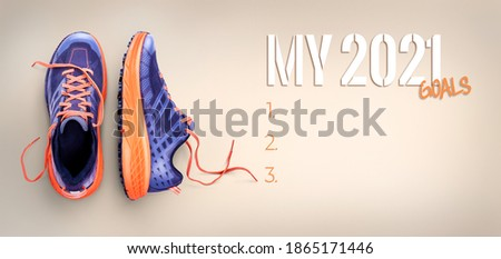 New year, new start business and health resolution concept for 2021. Purple and orange trainers on a pale beige background.