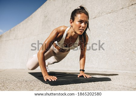 Fitness woman doing wide mountain climbers exercise. Female in sportswear exercising on fitness mat outdoors. Royalty-Free Stock Photo #1865202580