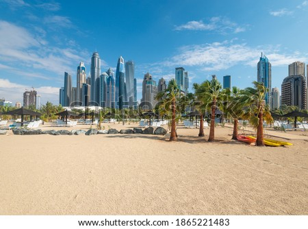 Sandy beach with  coconut palm trees against the background of Dubai Marina skyscrapers. Royalty-Free Stock Photo #1865221483