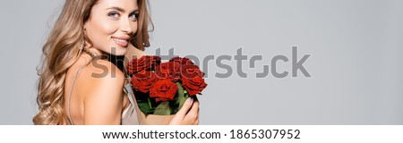 smiling elegant woman in dress with bouquet of red roses isolated on grey, banner Royalty-Free Stock Photo #1865307952