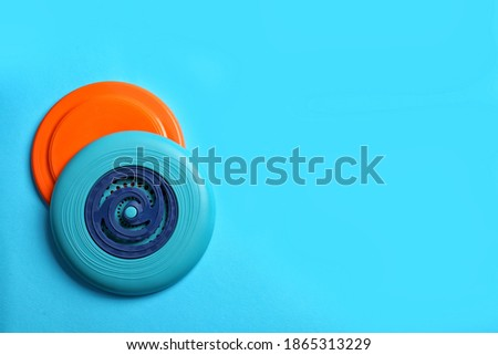 Plastic frisbee disks on light blue background, flat lay. Space for text