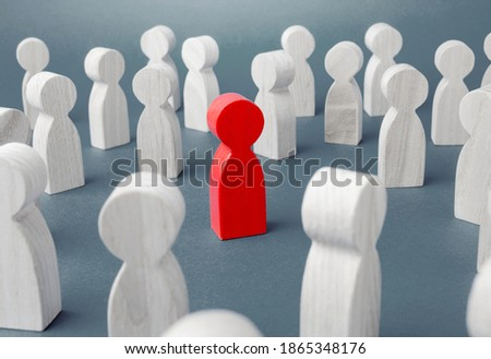 Red figurine of a man in a crowd of people. Stranger, eye-catching. Different, special. Infected carrying threat of spread of a pandemic. Collective immunity. Social distance. Intruder detection Royalty-Free Stock Photo #1865348176