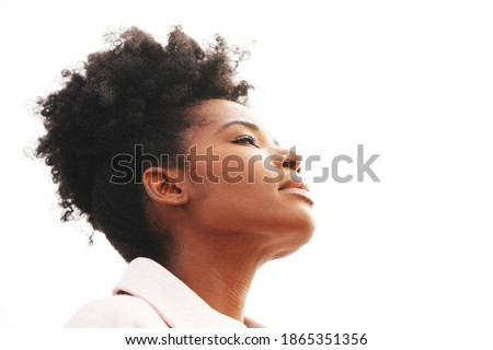Beautiful young majestic black woman wearing a light pink jacket with a high puff updo hairstyle holds her head back against a white background outside with eyes closed                               Royalty-Free Stock Photo #1865351356