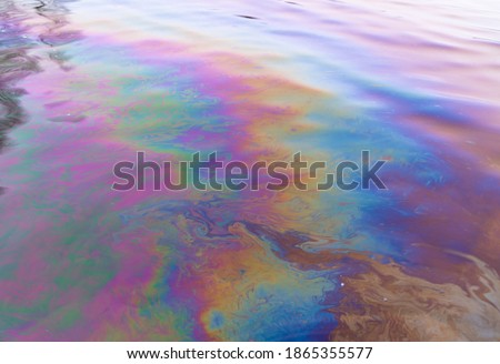 Oil petrol water pollution. Ecological disaster. Slick industry oil fuel spilling water pollution. Water with patches of gasoline and oil. Ecological catastrophe.  Concept of environmental problems Royalty-Free Stock Photo #1865355577